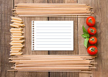Pasta, tomatoes and basil on wooden background Royalty Free Stock Photos