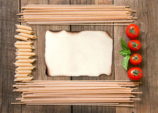 Pasta, tomatoes and basil on wooden background Stock Photo