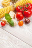 Pasta, tomatoes, basil on wooden table Royalty Free Stock Photo
