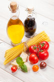 Pasta, tomatoes, basil on wooden table Stock Images