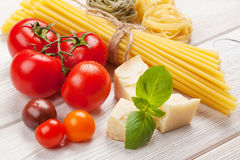 Pasta, tomatoes, basil on wooden table Stock Image