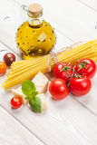Pasta, tomatoes, basil on wooden table Royalty Free Stock Photos
