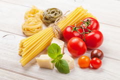 Pasta, tomatoes, basil on wooden table Royalty Free Stock Photography