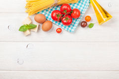 Pasta, tomatoes, basil on wooden table Royalty Free Stock Images