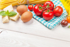 Pasta, tomatoes, basil on wooden table Royalty Free Stock Image