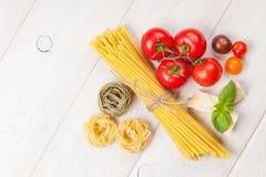 Pasta, tomatoes, basil on wooden table Stock Photos