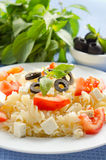 Pasta with tomatoes. And feta cheese decorated with olives and basil Royalty Free Stock Image