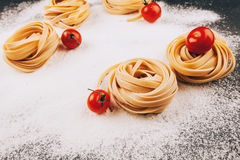 Pasta and tomatoes on flour. Raw pasta with tomatoes on a dark black background with scattered flour Royalty Free Stock Photos