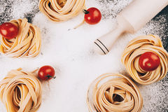 Pasta and tomatoes on flour. Raw pasta with tomatoes on a dark black background with scattered flour and a wooden rolling pin Royalty Free Stock Image