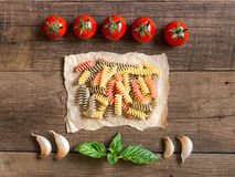 Pasta, tomatoes, garlic and basil on wooden background Stock Image