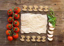 Pasta, tomatoes, garlic, herbs and paper Stock Photos