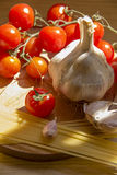 Pasta, tomatoes,garlic  on the table Stock Photography