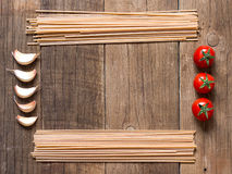 Pasta, tomatoes and garlic on wooden background Royalty Free Stock Image