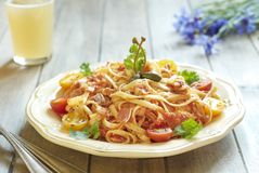 Pasta with tomatoes, ham, capers and cheese. Pasta with cherry tomatoes, smoked ham, capers and grated cheese royalty free stock photos