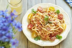 Pasta with tomatoes, ham and cheese. Pasta with tomatoes, ham, capers and cheese stock photo