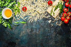 Pasta, tomatoes and ingredients for cooking on rustic background, top view, border. Royalty Free Stock Images