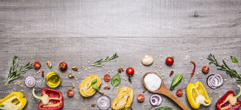 Pasta, tomatoes and ingredients for cooking on rustic background, top view, border. Italian food concept. Pasta, tomatoes ingredients for cooking on rustic Royalty Free Stock Photo