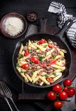 Pasta with tomatoes and meat on  dark rustic background. Stock Photography