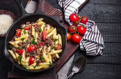 Pasta with tomatoes and meat on  dark rustic background. Royalty Free Stock Images