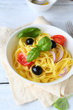 Pasta with tomatoes and olives in bowl Stock Image