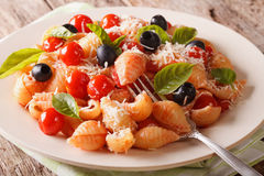 Pasta with tomatoes, olives and parmesan cheese close-up. horizo Stock Images