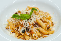 Pasta with tomatoes and olives. On a white plate Stock Images