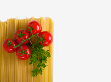 Pasta with tomatoes and parsley. Uncooked pasta with fresh tomatoes and parsley on a white background Stock Photo