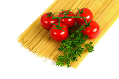 Pasta with tomatoes and parsley. Uncooked pasta with fresh tomatoes and parsley on a white background Royalty Free Stock Images