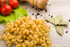 Pasta, tomatoes and pepper on a wooden background Stock Photography