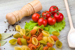 Pasta, tomatoes and pepper on a wooden background Stock Photo