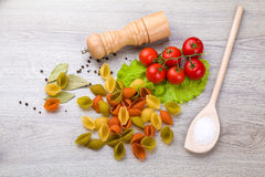Pasta, tomatoes and pepper on a wooden background Stock Images