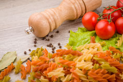 Pasta, tomatoes and pepper on a wooden background Royalty Free Stock Photo