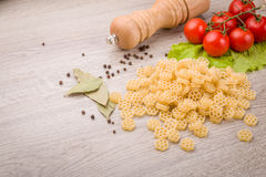 Pasta, tomatoes and pepper on a wooden background Royalty Free Stock Image