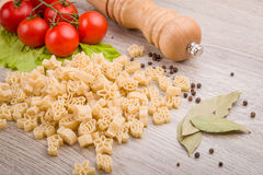 Pasta, tomatoes and pepper on a wooden background Royalty Free Stock Photography