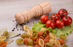 Pasta, tomatoes and pepper on a wooden background Royalty Free Stock Photos