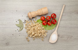 Pasta, tomatoes and pepper on a wooden background Royalty Free Stock Images