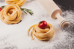 Pasta, tomatoes, rosemary on black. Raw pasta with tomatoes and rosemary on a dark  black background with scattered flour and a wooden rolling pin Royalty Free Stock Photography