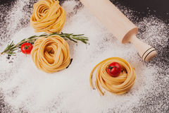 Pasta, tomatoes, rosemary on black. Raw pasta with tomatoes and rosemary on a dark  black background with scattered flour and a wooden rolling pin Royalty Free Stock Photo