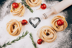 Pasta, tomatoes, rosemary on black. Raw pasta with tomatoes and rosemary on a dark  black background with scattered flour and a wooden rolling pin Royalty Free Stock Photos