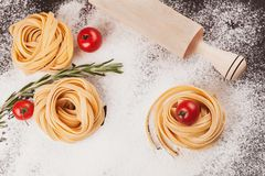 Pasta, tomatoes, rosemary on black. Raw pasta with tomatoes and rosemary on a dark  black background with scattered flour and a wooden rolling pin Stock Images