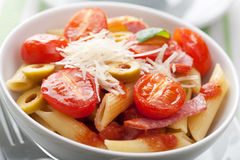 Pasta with tomatoes and salami Stock Photos
