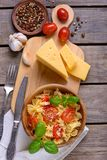 Pasta with tomatoes and sauce with basil. On wooden background Stock Photography