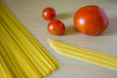 Pasta and tomatoes. On a table.  Ingredients for cooking Royalty Free Stock Images