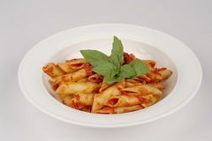 Pasta with tomatoes in white plate. Italian pasta with tomatoes in white plate Royalty Free Stock Photography