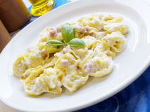 Pasta Tortellini And Ham Cream. Italian cuisine background. Delicious stuffed pasta tortellini with cream, ham and basil on white dish Royalty Free Stock Photo