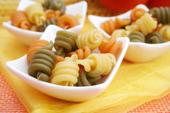 Pasta tricolore. Some fresh italian pasta in yellow, orange and green stock photos