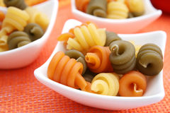Pasta tricolore. Some fresh italian pasta in yellow, orange and green royalty free stock photos