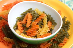 Pasta tricolore. Some italian noodles in green, orange and yellow royalty free stock photo