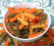 Pasta tricolore. Some italian noodles in green, orange and yellow royalty free stock photos