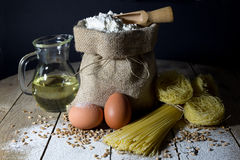 Pasta, Two Eggs, Jute Bag Filled with Flour, Wooden Spoon and Olive Oil in Glass Bottle on Wooden Table, Black Background Stock Images